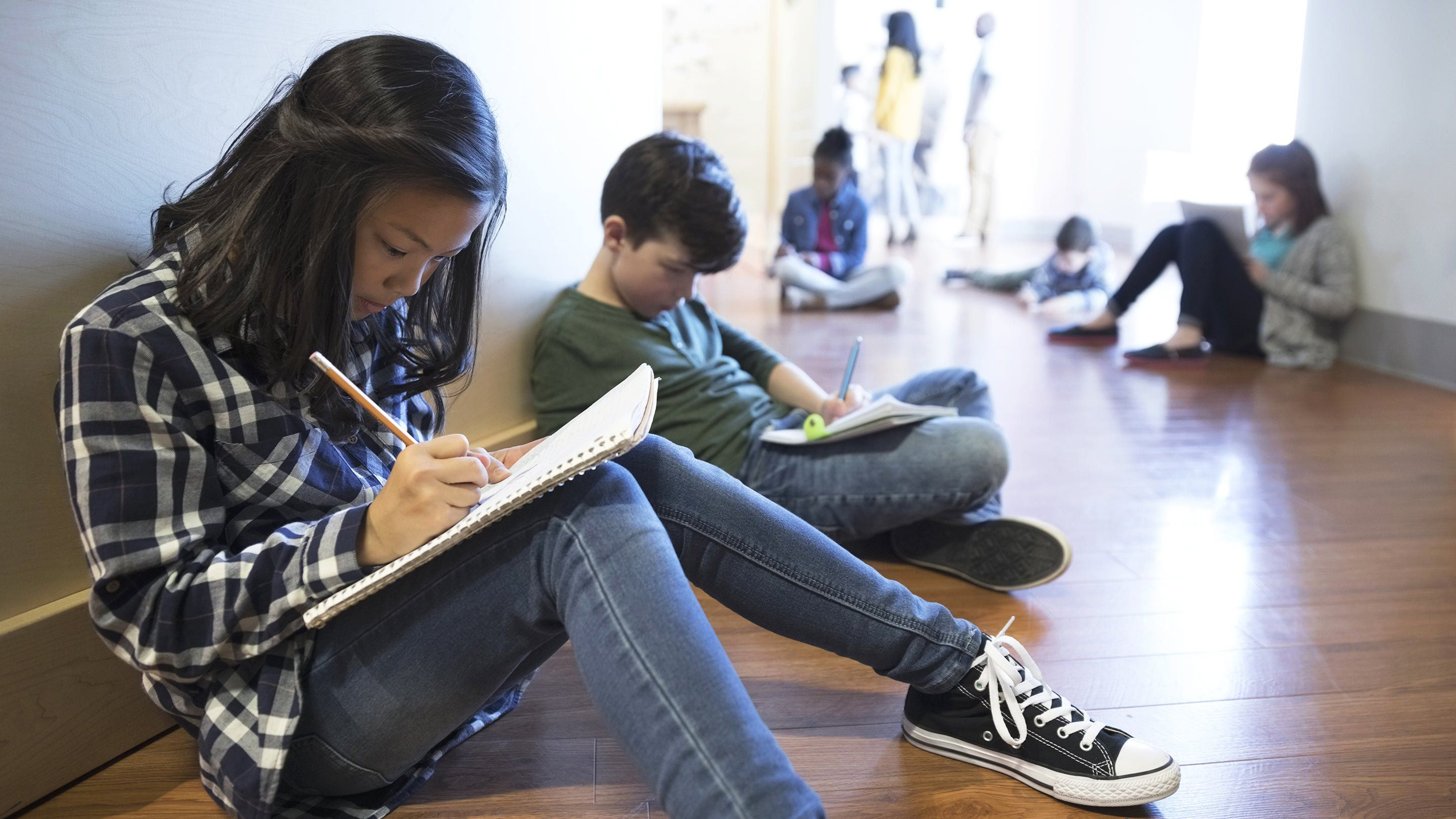 Students work independently while sitting in a school hallway.