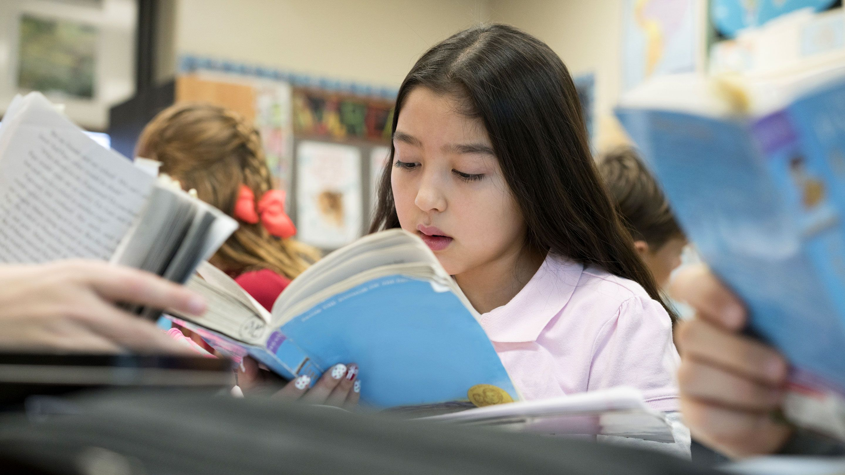 A young girl is deeply engaged in reading in a class full of students.