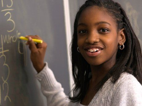 Young African American girl smiling holding chalk in front of a black board