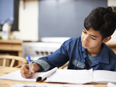 A photo of an elementary-school boy writing in his notebook.