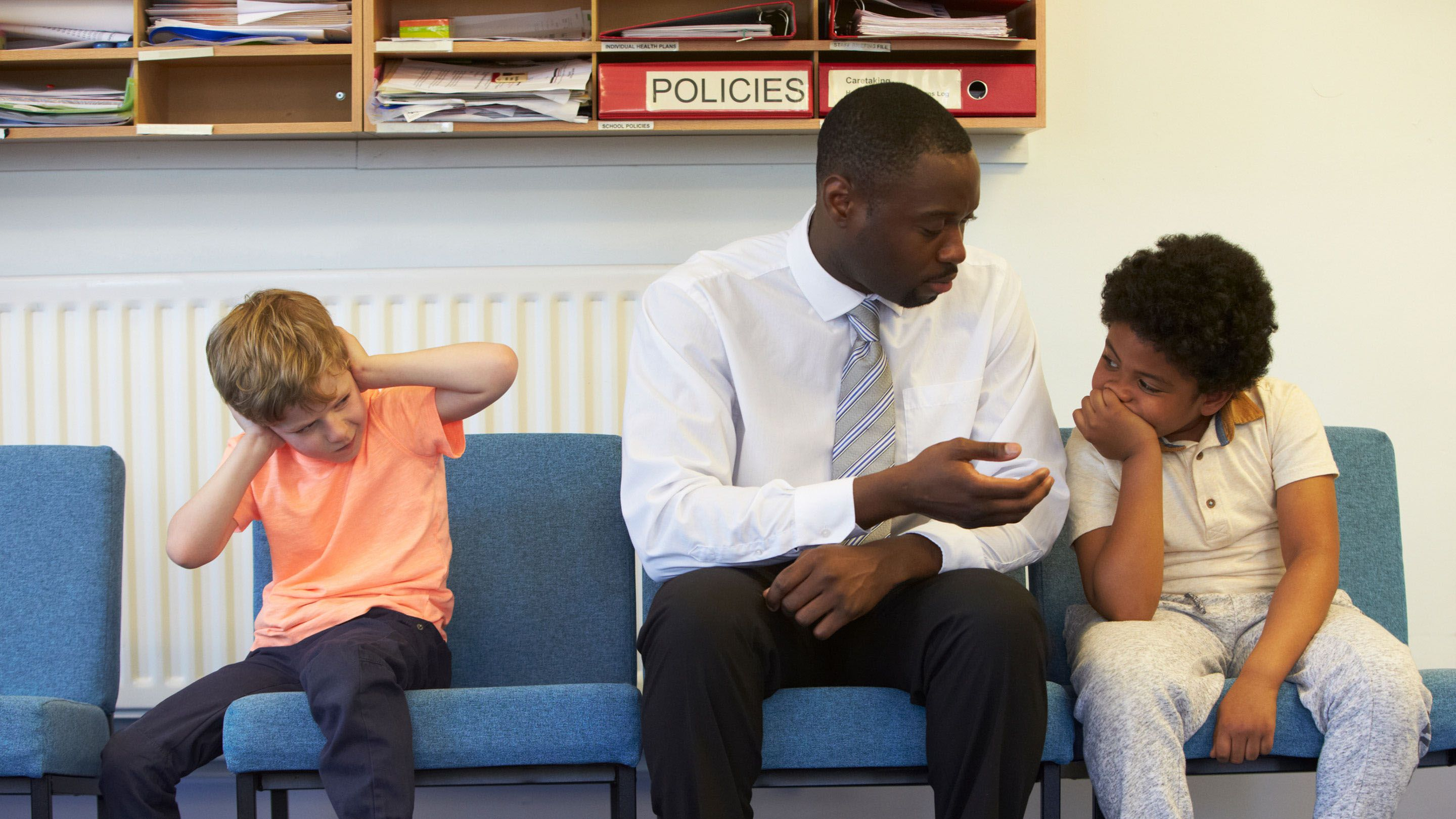An adult male in a white button up shirt, tie, and black pants is sitting between two young boys in chairs against the wall of an administrative office. He's talking to one of them, while the other boy has his hands over his ears.