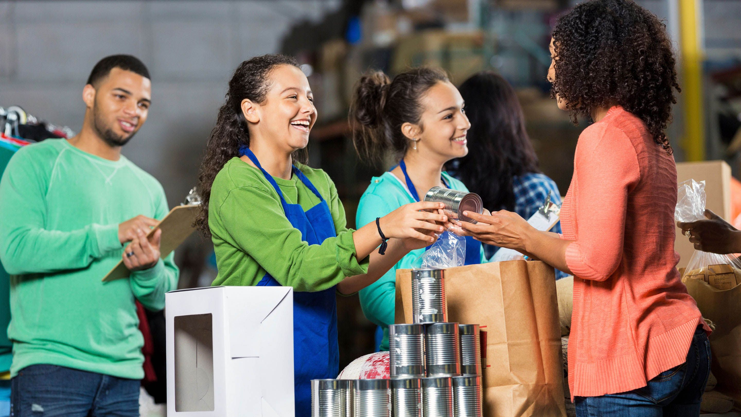 Three teenagers with one adult handing out canned foods to those in need.