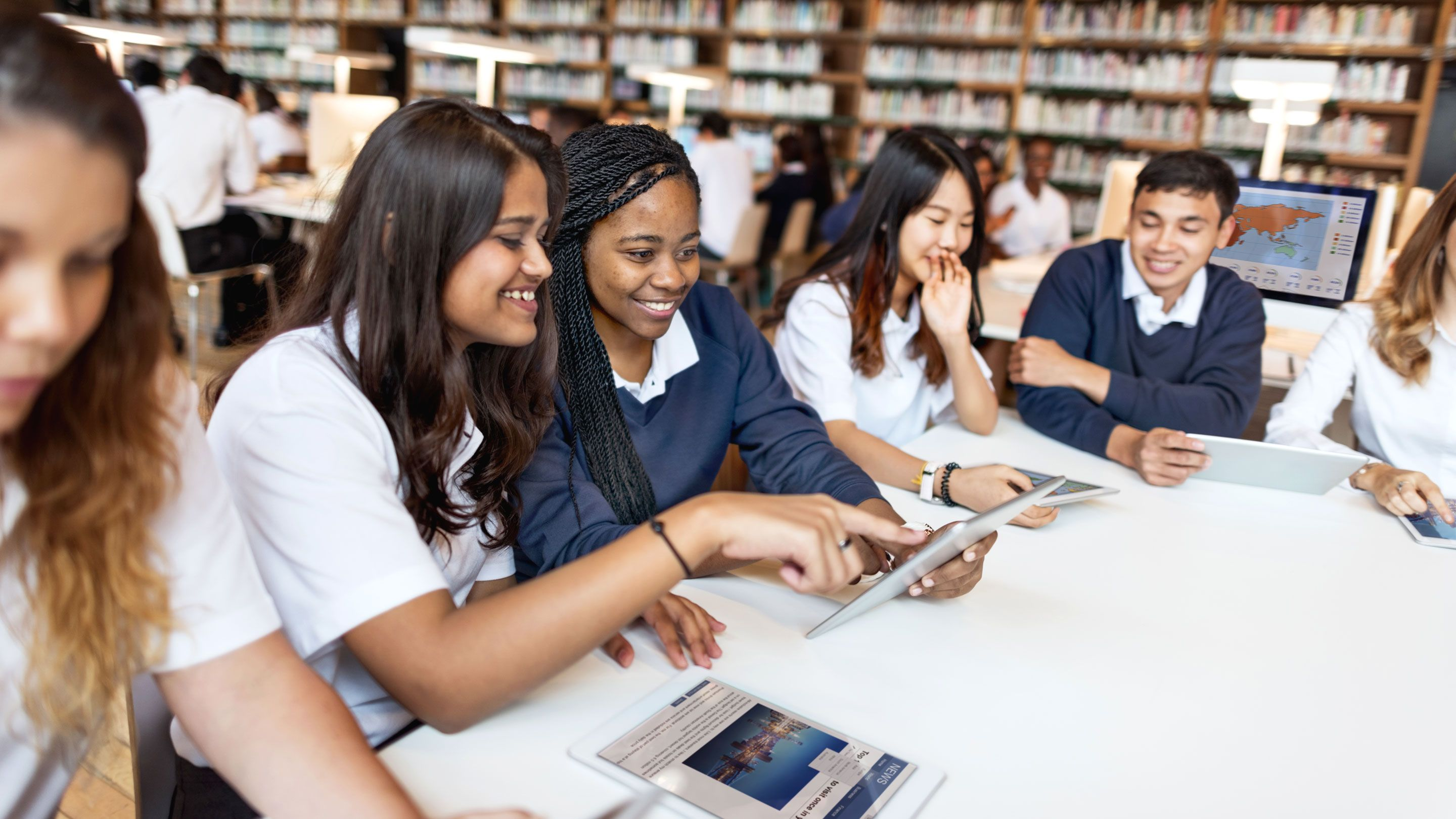 Five teenaged students are seated at a table looking at computer screens, talking, and smiling.