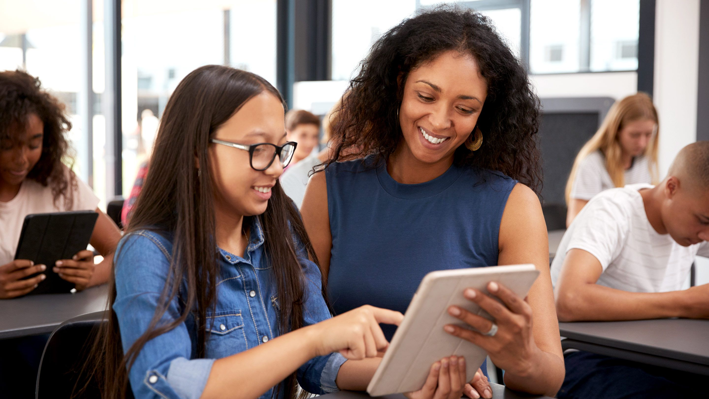 A female teacher and twelve-year-old girl are standing, smiling, and looking at a daily planner together.