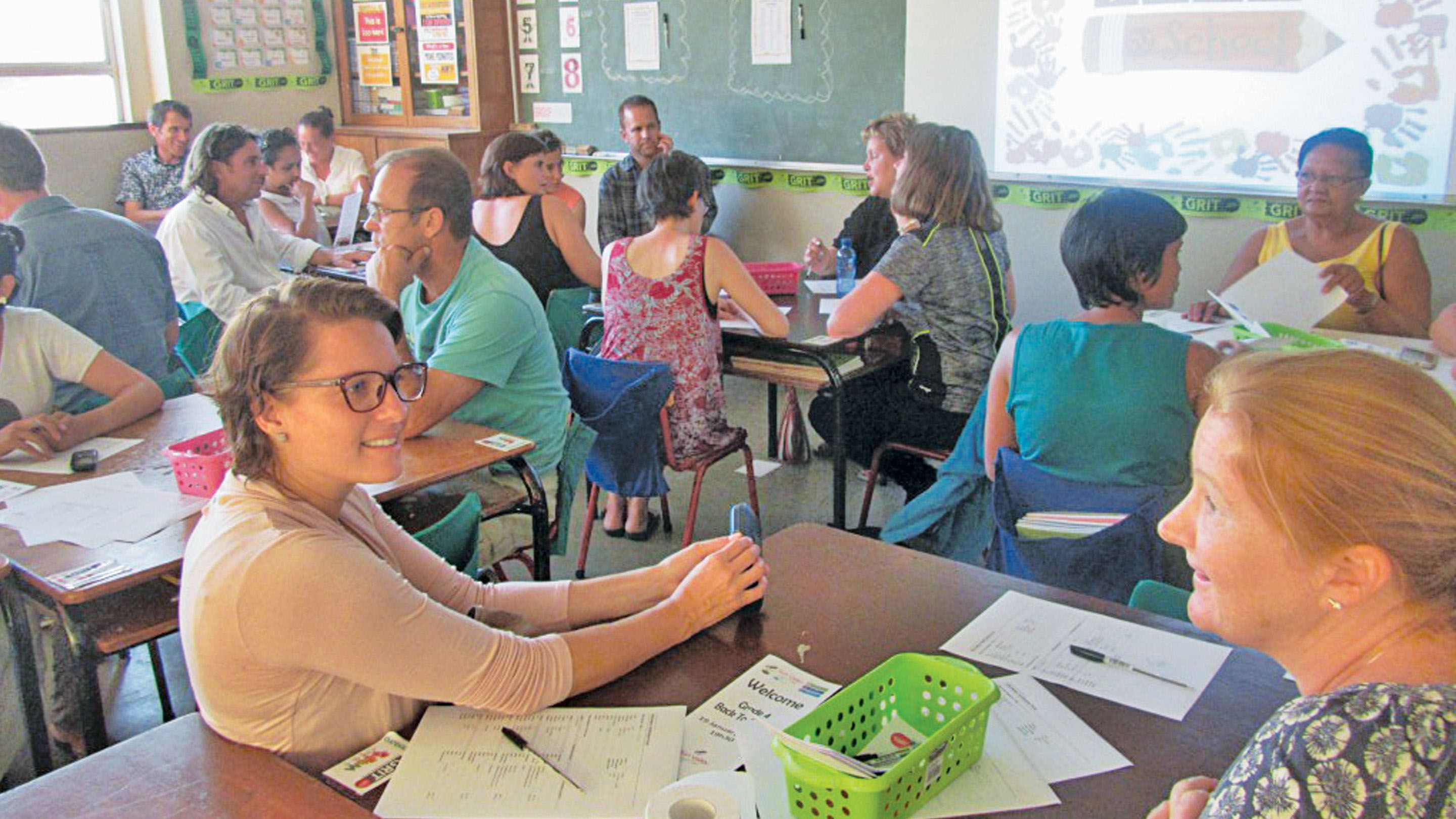 A classroom filled with teachers talking to each other while seated