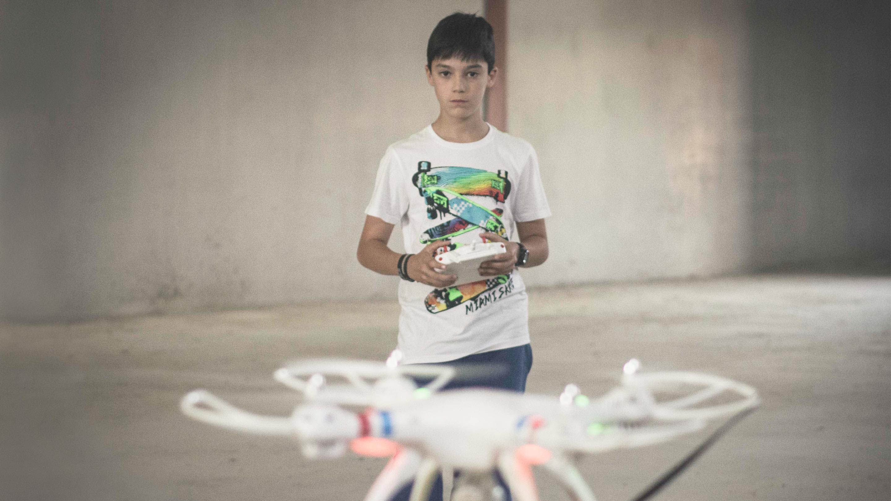 A young boy is standing in an empty cement building. He's playing with a flying, remote-operated drone.