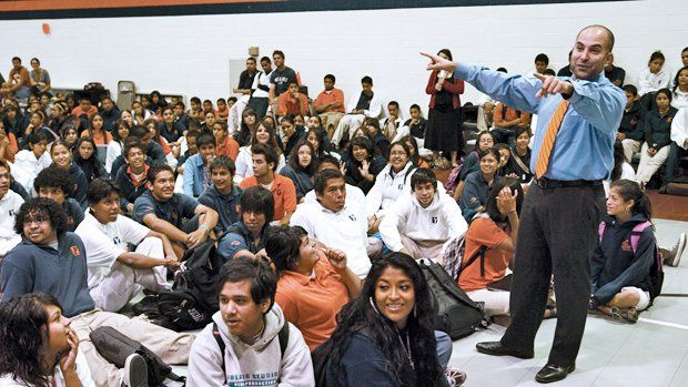 Principal with arms raised talking to a gym full of kids sitting on the floor