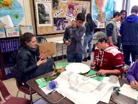 Two boys and a girl around a table working on a project