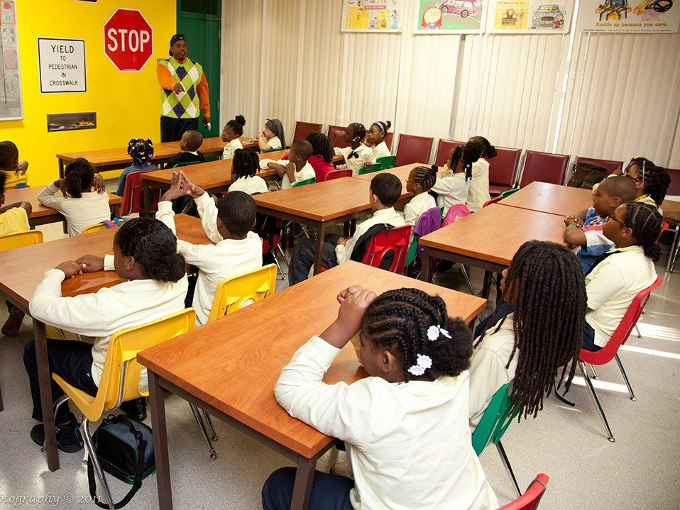 "A group of young students are sitting in a classroom looking towards an adult male. At the front of the class, the wall is yellow. A red and white stop sign is hanging on the wall next to another sign that says, ""yield to pedestrian in crosswalk."""