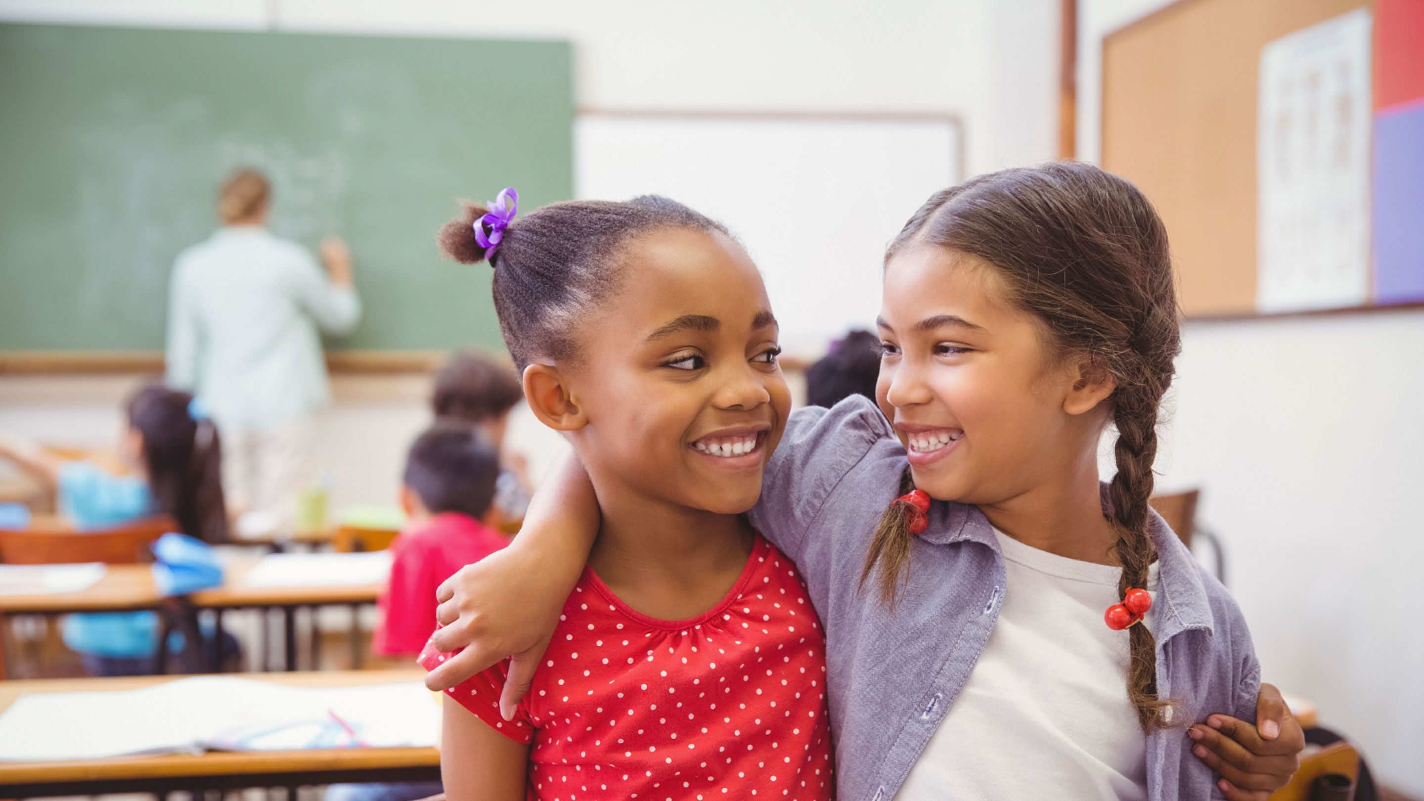 photo of two students smiling at each other in a classroom
