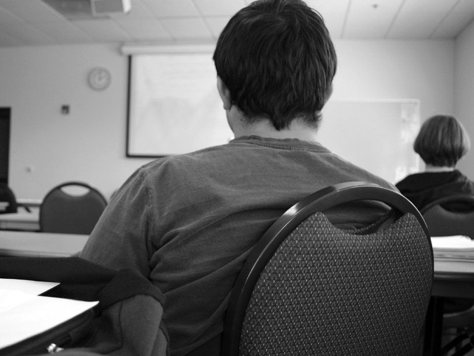 A black and white closeup of the back of a young man sitting at a long table towards the back of a classroom. He's looking toward the front of the classroom, and there's one other student sitting two tables ahead of him to the right.