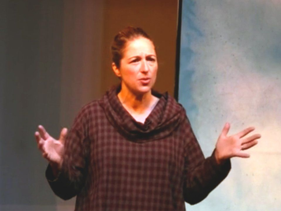 An adult woman with her hair pulled back in a ponytail is wearing a cowl neck maroon and beige checkered hoodie, standing with her elbows at her sides and her hands raised, as if she's addressing an audience.