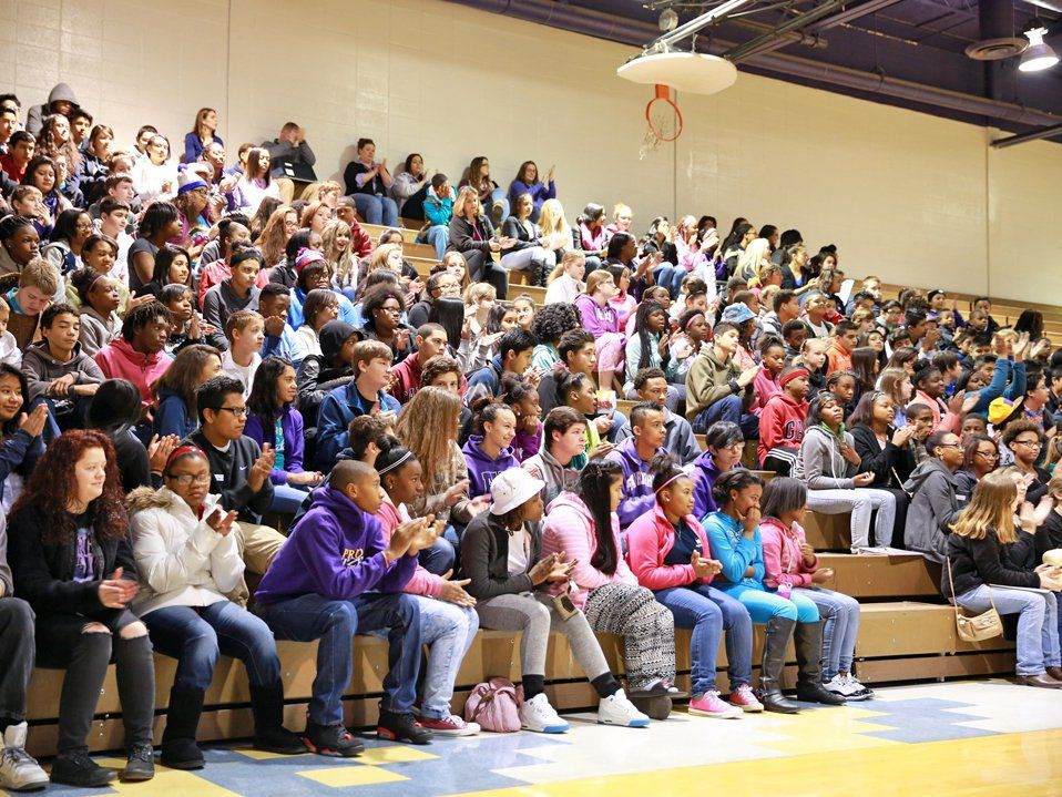 In the multipurpose room, a large group of middle school students fill one side of the bleachers, some clapping.