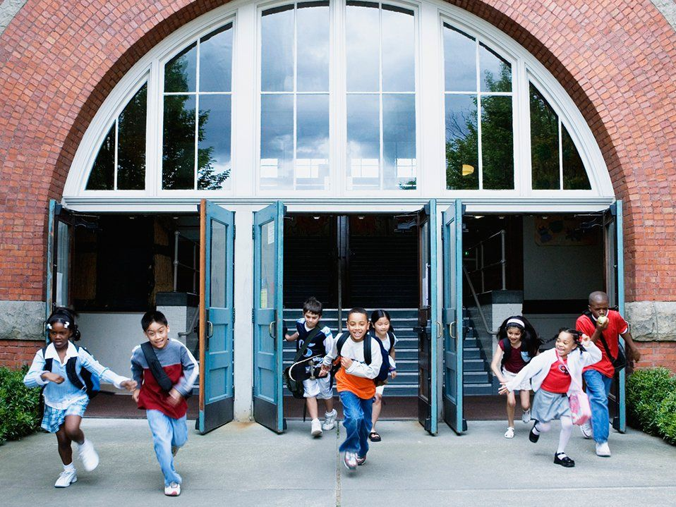 Eight elementary-age students are smiling, running out of the school building through three opened doors.