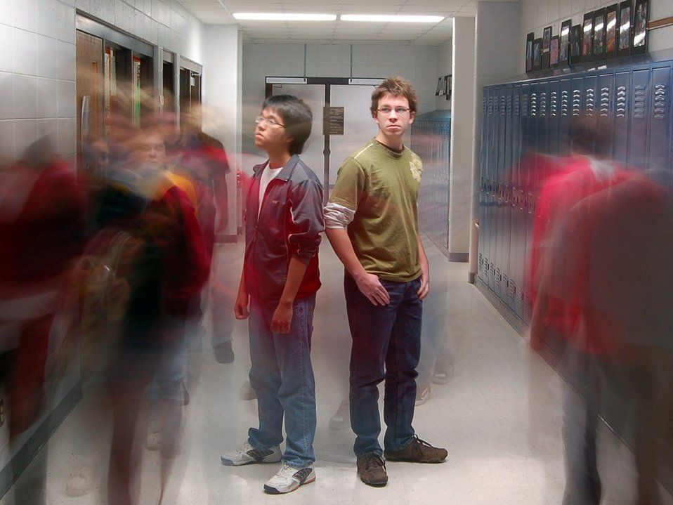 Two students are standing back to back in the middle of the school hallway. Other students are walking past them, blurred, as if to capture all the students walking through the hallway throughout the day.