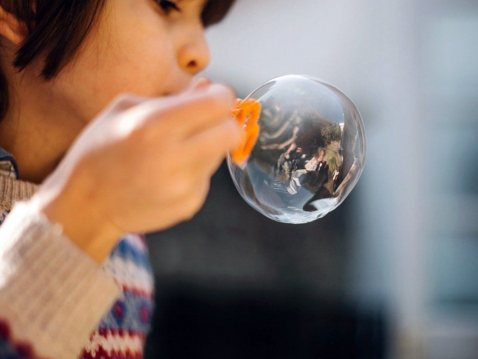 A closeup of a young kid blowing a big bubble. He's to the left of the photo, the top of his head out of frame, and his arm is in front of his face holding an orange plastic device to blow bubbles.