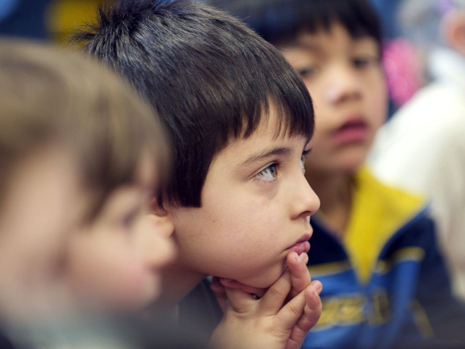 A closeup of the side of a young boy's face. He's looking in front of him. Other young kids are sitting around him, but they are out of focus.