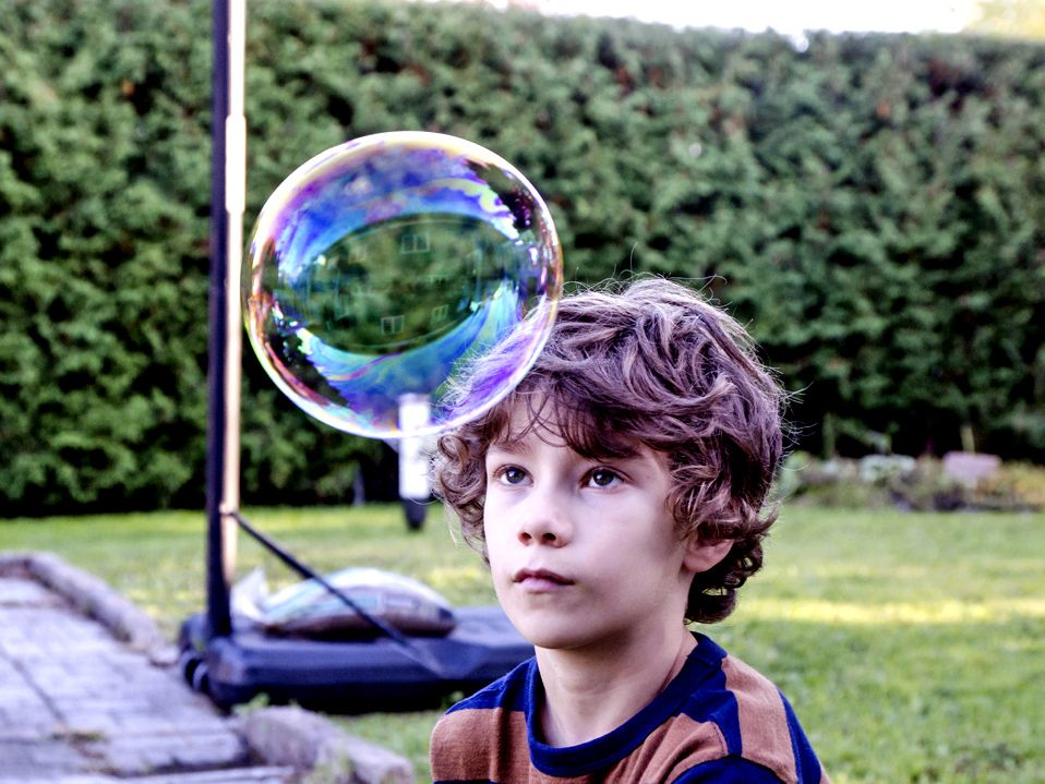 A young boy wearing a striped blue and orange t-shirt is looking at a bubble in front of his forehead that is almost the size of his head. He's outside. Behind him is grass next to a brick floor with a basketball hoop and a tree fence.