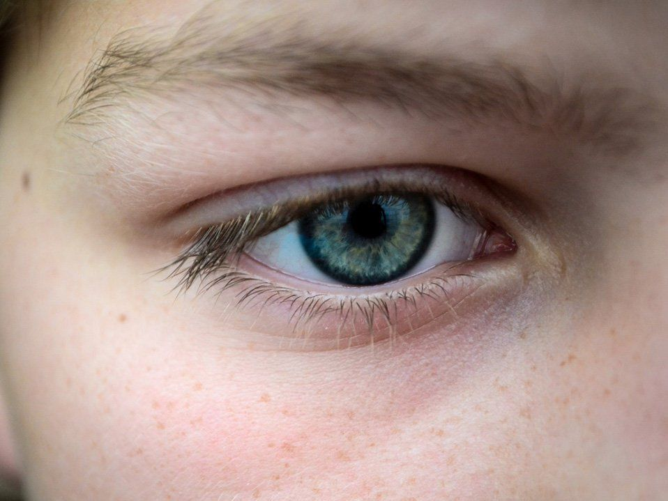 A closeup on someone's eye. Their eye is green and blue. Their eyebrows and eyelashes are dark blond.