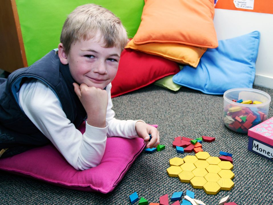 A young boy is lying on the floor, his elbows on a small, square pink pillow. He's looking at the camera with colorful shaped blocks in one hand, and more on the floor.