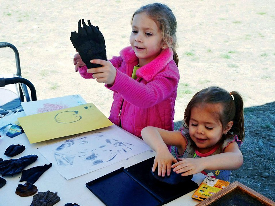 Two young girls are standing on grass next to a table with paper, stamp ink, crayons, and glove-like cloth that they're using as stamps. One girl is pushing her glove into the stamp ink, and the other girl is holding up her glove.