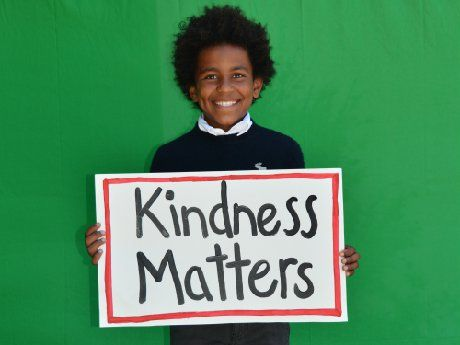 "photo of a student holding a sign which reads ""Kindness Matters"""