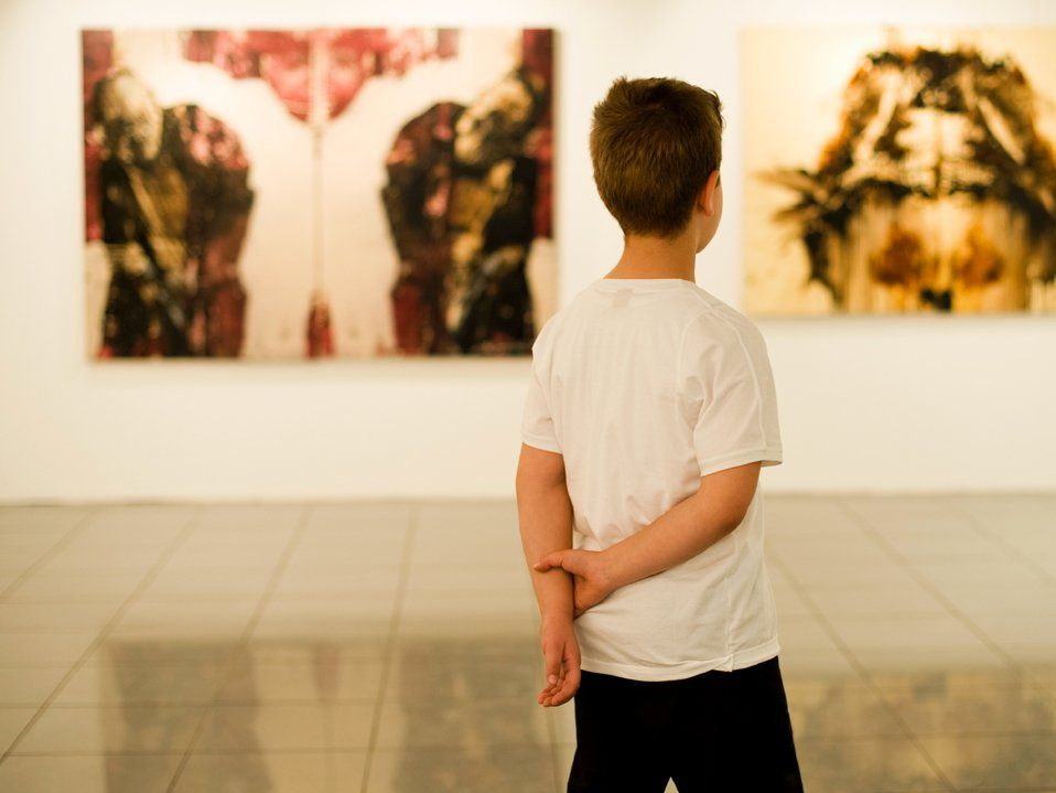 A young boy in a white t-shirt is standing in a museum, with his hands behind his back, looking at artwork.