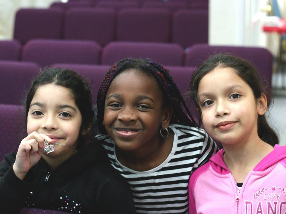 Three young girls are standing side-by-side; the girl in the middle has her arms around the other two. They're all smiling, looking directly at the camera. Behind them are rows of purple theater seats.