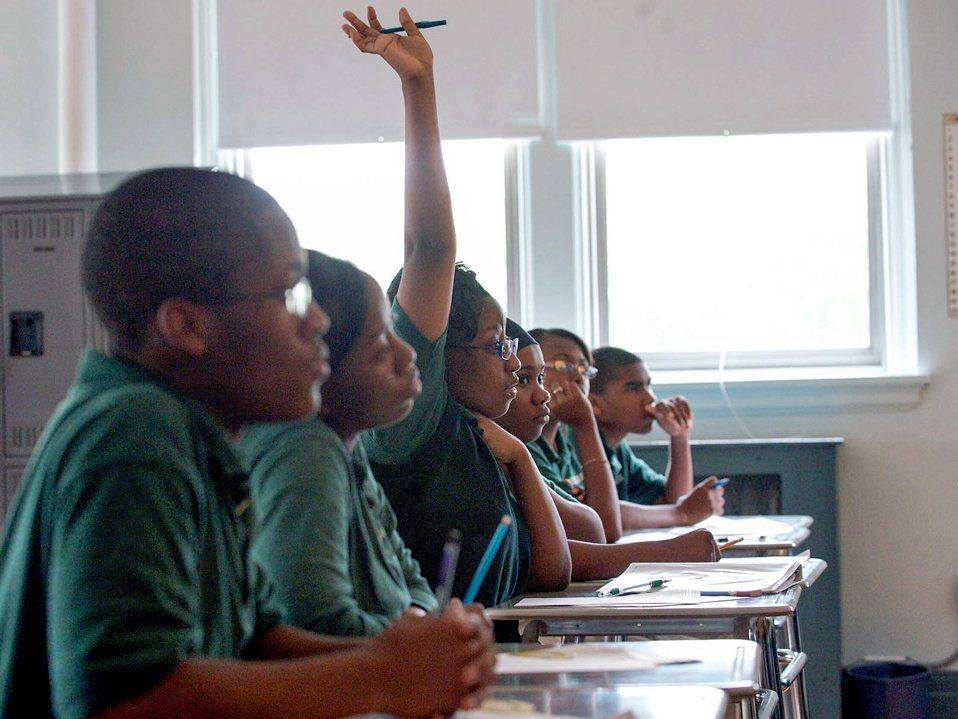 Six high school students, all in green shirts, are sitting in a row at individual desks looking towards the front of the class. One of them has their hand raised.