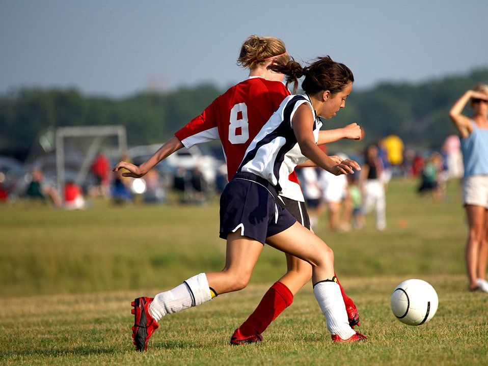 Two teen girls are fighting for a ball on the soccer field.