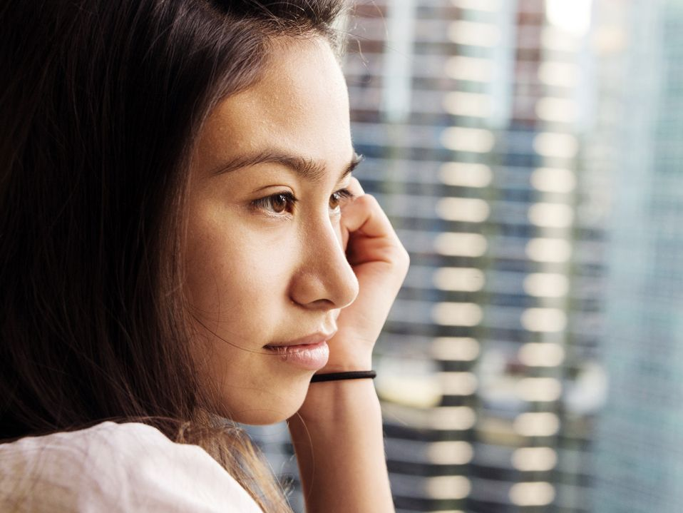 A closeup of a side profile of a young female student looking out a window. Her left cheek is resting against her left hand, and there's a hair tie around her wrist.