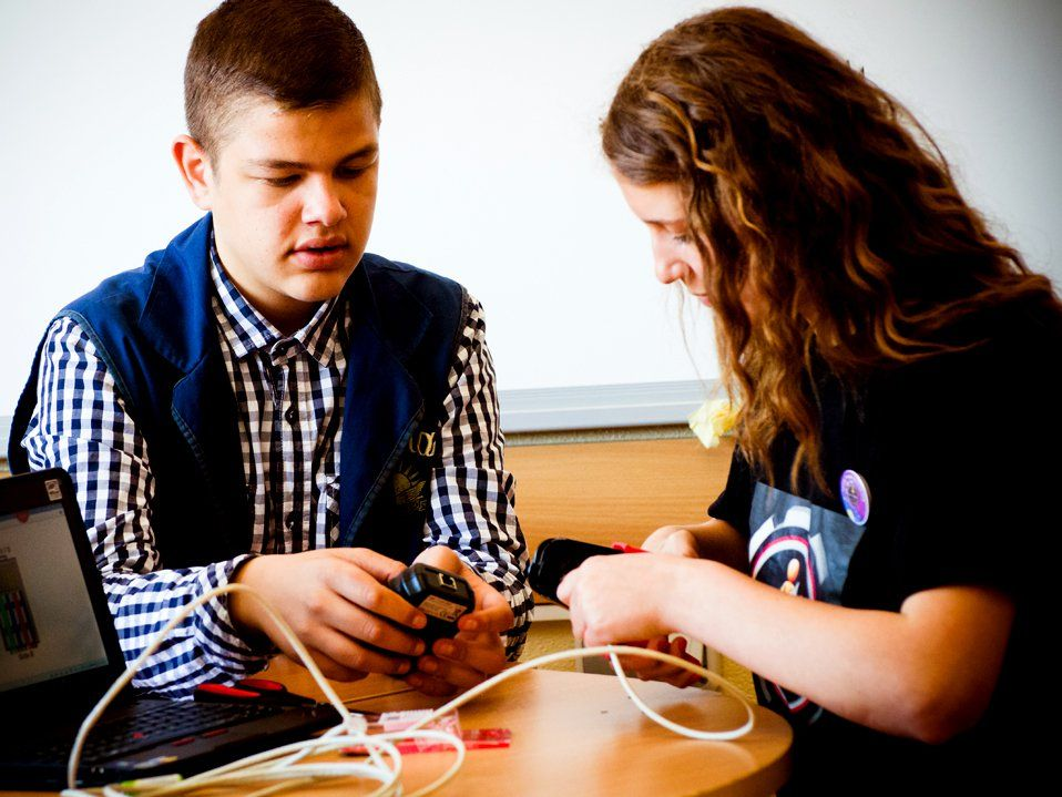 Two teenagers are sitting at a table with a laptop, one is holding a cell phone charger and the other is holding a cell phone, connecting it to a white wire.