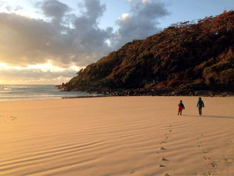 Two young kids are walking on the sand along the beach, the ocean to their left, and a hill covered in trees in front of them.