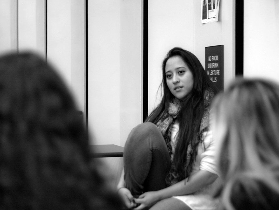 A black and white image of a young, long-haired woman sitting on the floor against a white wall, looking towards two other women sitting on the floor.