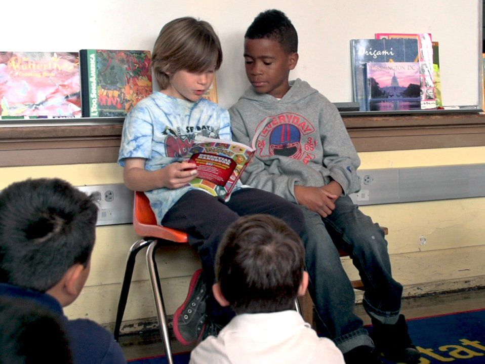 Two young students are sitting in chairs against the wall with a whiteboard behind them. They're reading a book to the rest of the class who are sitting on the carpeted floor in front of them.