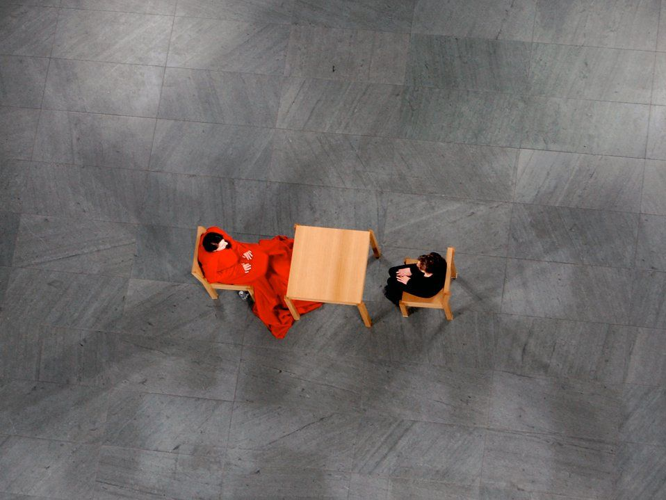 High, overhead view of two people sitting at a table on a patterned concrete floor with no one else around