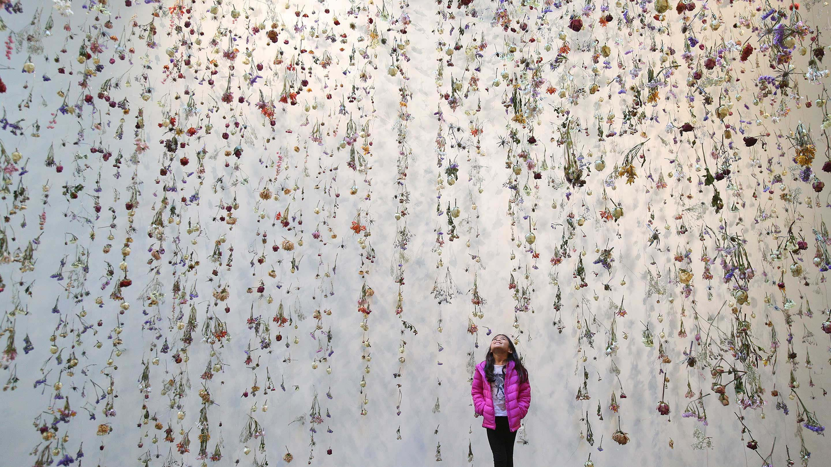 photo of a student in gallery filled with hanging flowers