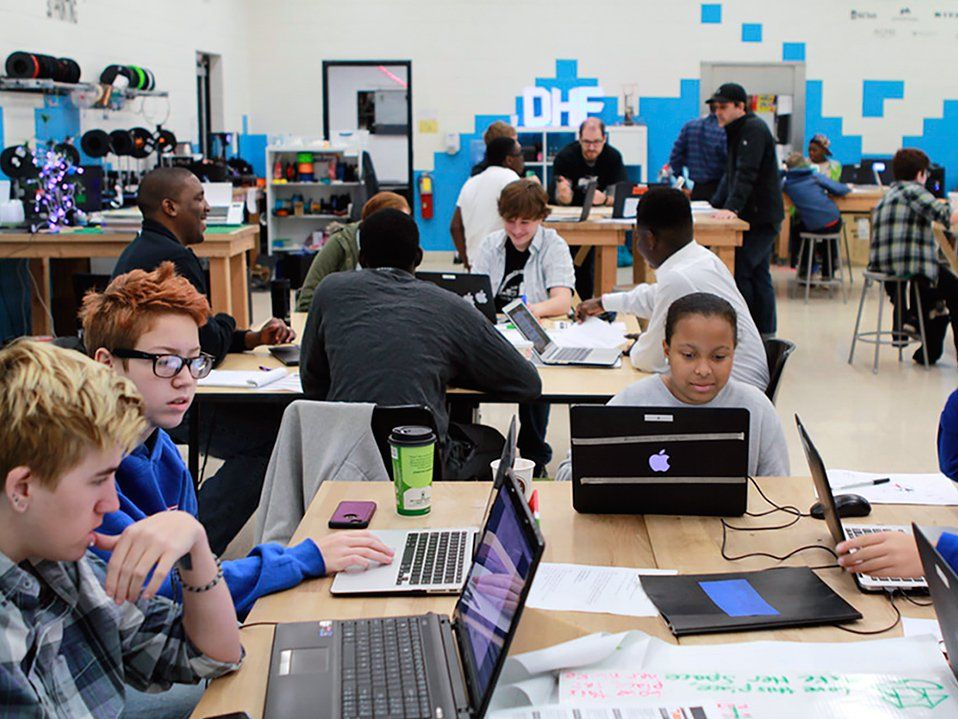 A classroom filled with high school students sitting at large rectangular tables, working together on laptops.