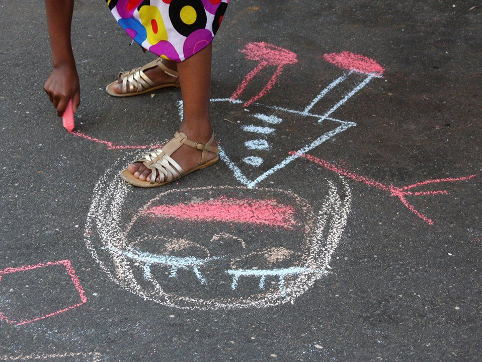 A girl in golden sandals and a colorful polka dot dress is standing on cement, bending over, holding pink chalk, drawing a smiling girl.