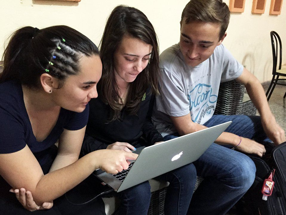 Three high-school teens are sitting next to each other on a couch, two girls on the left and a boy on the right. The girl in the middle has a laptop on her lap that they're all looking at.