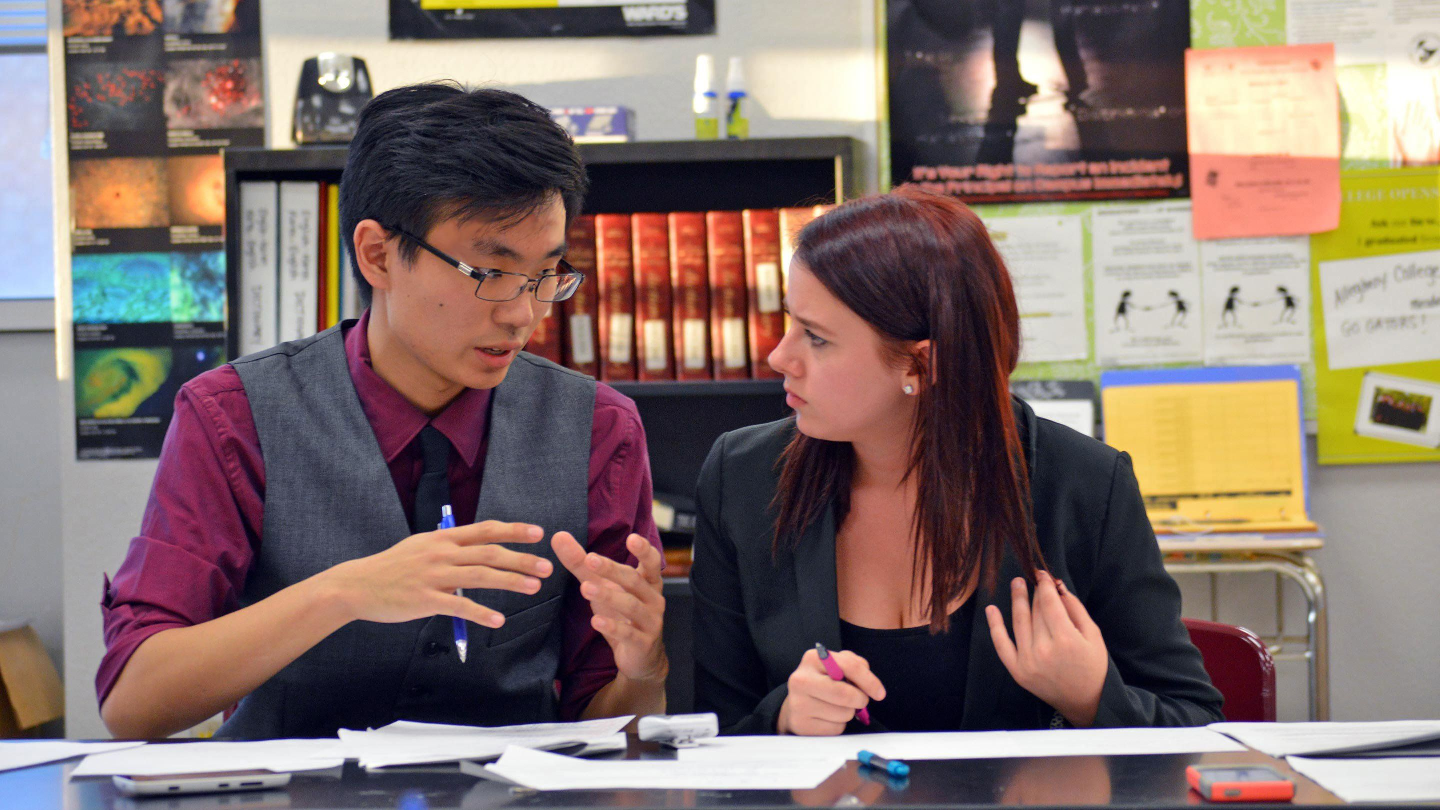 A teenage boy and girl dressed in business clothes are sitting at a classroom table -- covered with opened binders filled with paper -- talking to each other.