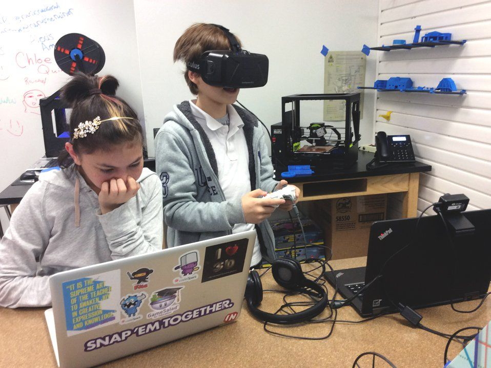 A young girl is sitting at a classroom table working on her laptop. A young boy is standing next to her with high-tech eye goggles on, a video game controller in his hands, and he's looking at a laptop with a video camera connected on the top.
