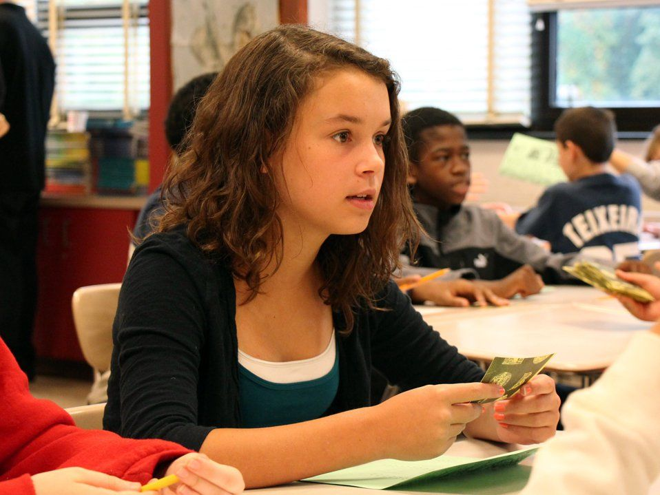 A young girl is sitting in class, looking straight ahead with a playing card in her hand and a green sheet of paper on her desk. Other students in the classroom are sitting with green sheets of paper and playing cards about.