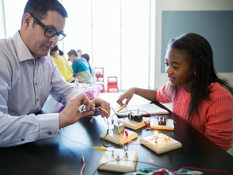 A female student and a male teacher are sitting at a raised table together putting wires together to turn on small light bulbs connected to square pieces of wood.
