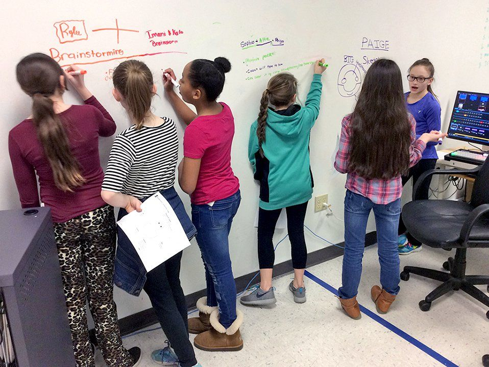 "Six young, female students are standing by a whiteboard wall. They're creating a process outline and delegating each task by writing their name next to each step. The names Rylee, Imani, and Kate are written text to ""brainstorming."""