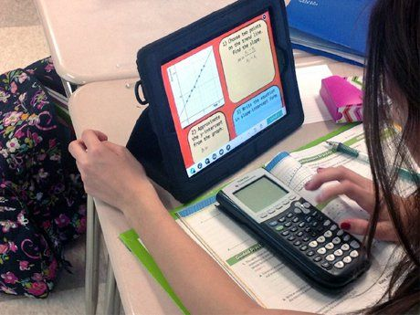 photo of a student using a calculator and tablet computer