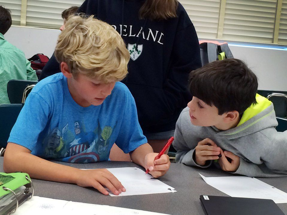 Amidst other students, two young boys are sitting at their classroom table, working on an assignment together.