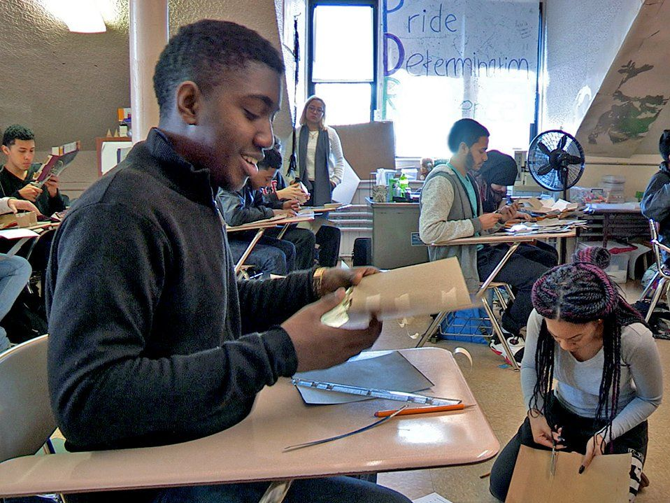 A high school boy is sitting at his desk, smiling, folding a piece of cardboard with pieces of tape on it. The class is filled with students at their desks or on the floor cutting and taping together pieces of cardboard.