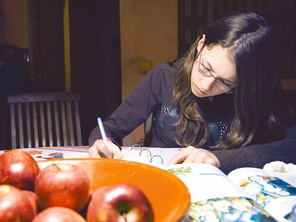 A young girl with glasses is sitting at her kitchen table writing. There's a bowl of apples on the table, next to an opened text book, next to an opened binder with lined paper.