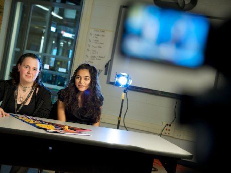 Two young girls are sitting at a table in a classroom being filmed with a light behind them.